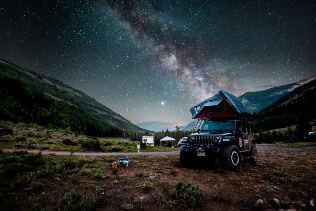 Jeep with a rooftop popup tent and the Milky Way in the background across the sky