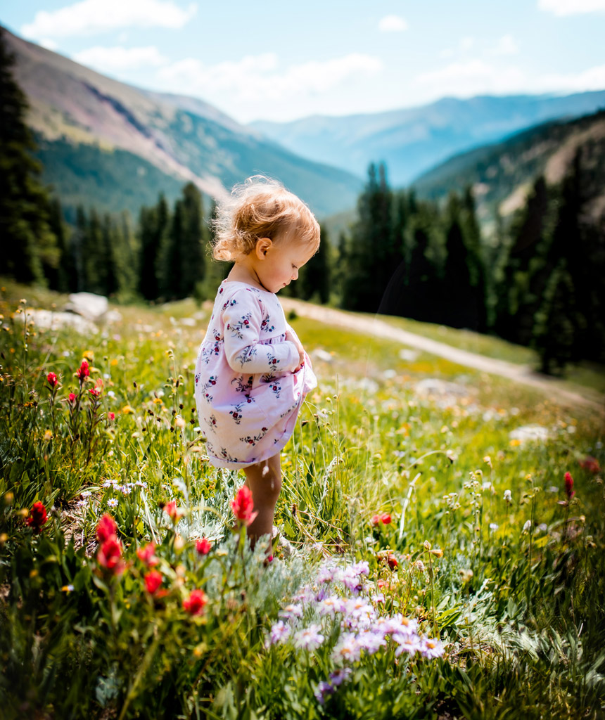 Toddler standing in a field of wildflowers at Herman Gulch